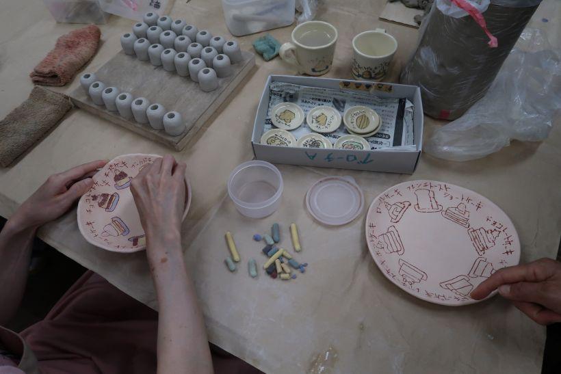 陶芸の作業を見学。利用者が陶芸用パステルをお皿に絵を描いている。
